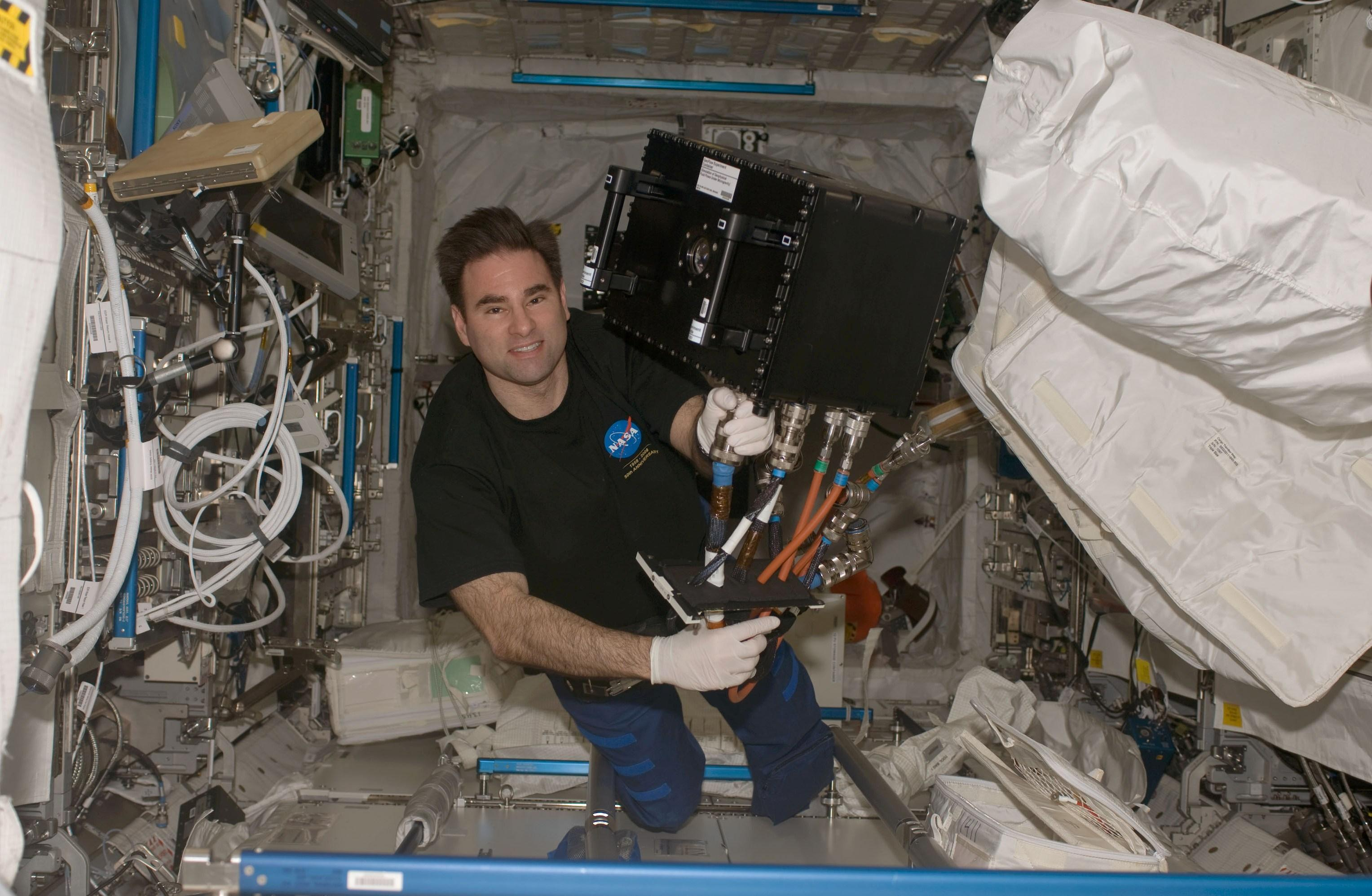 Astronaut Gregory Chamitoff as he works to install the Fluids Science Laboratory (FSL) Geosynchronous Earth Orbit (GEO) Experiment.