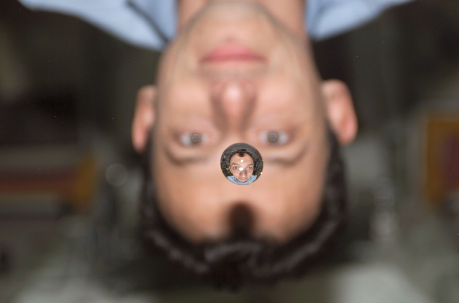 Pedro Duques watches a water bubble float between him and the camera, showing his image refracted