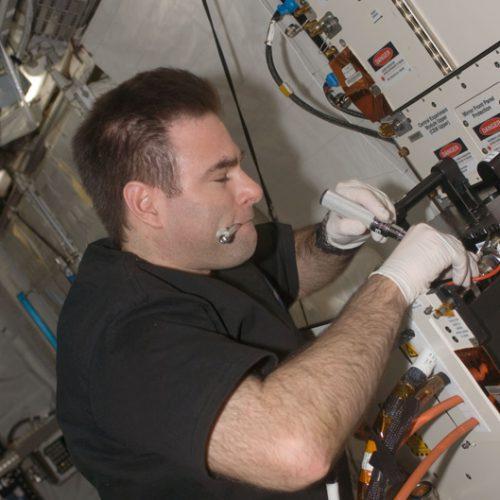 Astronaut installing experiment container in Columbus module